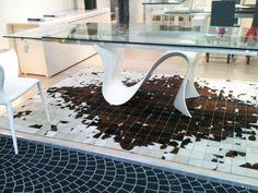 Un tavolo totalmente di vetro con una base dalle forme ondeggianti