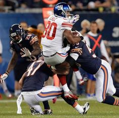 New York Giants wide receiver Victor Cruz (80) is tackled by Chicago Bears safety Chris Conte (47) and linebacker James Anderson
