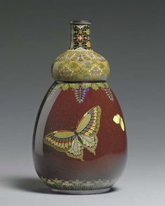 A Cloisonné Enamel Bottle Meiji period (circa 1890), signed Kyoto Namikawa [workshop of Namikawa Yasuyuki, 1845-1927] The double-gourd bottle worked in silver wire and polychrome enamels with butterflies and wisteria against a mottled brown and black ground, the shoulder designed with bees, wisteria and foliate scroll on a mustard-yellow ground, the neck with floral lozenges on black and the foot ringed with a band of irises; mounts silver; foot incised with the initials M.A.