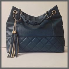 "Black Rivet Leather Handbag Excellent used condition. Like new! Large dark turquoise tote bag with gold hardware. Exterior has 1 back zip pocket. Quilting on the front bottom. Interior is lined with 2 zip pockets. Strap has chain detail with a drop of 8"". Wilsons Leather Bags Totes"
