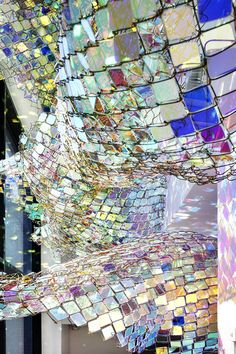 """sculptor soo sunny park, """"capturing resonance"""" art installation. park created the undulating textile by inserting thousands of acrylic squares into chain link fencing."""
