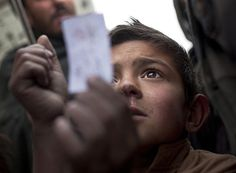 March 4, 2012 An Afghan refugee boy holds up his food voucher as he fights with others to get a ration from a truck organized by the World Food Program in Kabul, Sunday. Anja Niedringhaus/AP