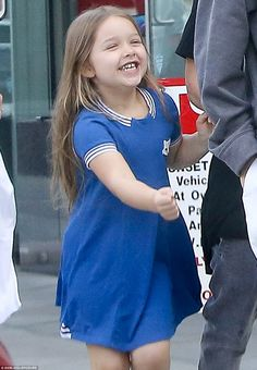 Babe in blue: Harper Beckham was in a giddy mood as she left the gym in West Hollywood with her family on Wednesday