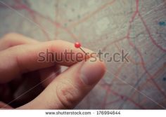 Close up on a hand placing a pin on a map - Shutterstock stock photo