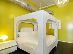 Retro Bedroom: Although the bed is truly the focal point in this bedroom, white accents and bright yellow bring out the trendy modernist in the room.  From HGTVRemodels.com