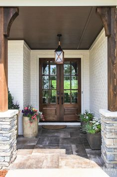 Double glass front doors with rock and rustic front porch