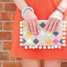 Clutch bag designed by @cotton_clara using thick wool in bright colours and neons and greys. Stitched on plastic canvas with pom pom trim
