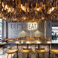let's mEAT here! this burger cafe in poltava, ulkraine. the #interior concept is influenced by the burger itself, with a ceiling of undulating timber rods representing minced meat.  see more projects by @yod_studio on #designboom! #restaurantinteriors image by andrey avdeenko