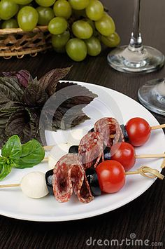 Appetizer of salami with mozzarella, olives, cherry tomatoes on skewers with basil