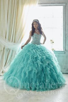 Ruffles of tulle and sparkling tulle pour out of a Basque waistline. Beautifully decorated on the bodice with beads aligned in tear-drop pattern. Download the Quinceanera Collection by House of Wu siz