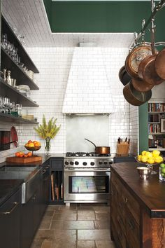 Tan tile floor + green walls & ceiling + white tile backsplash + wood island + black countertop & shelves + stainless steel range + hanging copper pots = the kitchen