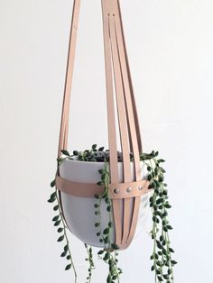 Modern leather plant hanger, ceiling planter, minimalistic hanging planter made from nude vegetable tanned leather. This leather is very thick and can carry a lot of weight. On top of the hanger is a thick metal ring. Dimensions: Diameter 16 centimeters / 6 Height: 65 centimeters / 25 Pls. note: the white pot is included, the plant is not. There is no drainage hole in the pot. It can take up to two weeks for me to send you the product, because I dont have a lot of stock. But no wor...