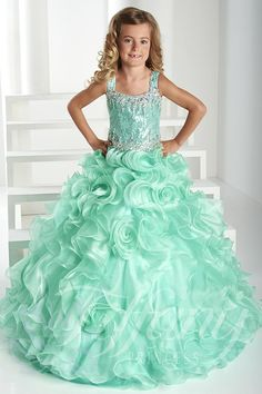 Make your princess a Tiffany Princess in this stunning, full-length, sweet girl's pageant dress. Sequins sparkle all along the bodice, while AB stones glisten around the straps and neckline. The AB stones create a pattern along the neckline and waistline for a truly eye-catching design. Layers of ruffles with flowers complete the full ball gown skirt. Lace-up back. Crystal Organza. Please note that the angel blue color is mint in color. The dress photo reflects actually color that you will…
