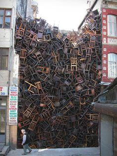 """Artist Doris Salcedo filled the empty space between two buildings in Istanbul with 1,550 wooden chairs stacked seemingly haphazardly, but with a message that was more carefully constructed. Salcedo said the 1,550 chairs evoke """"the masses of faceless migrants who underpin our globalized economy."""" Sit on that."""