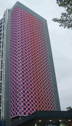 One of Ban-Qiao City's newest and unique apartment towers. The building's media lighting system is comprised of customized flexible LED units housed within the key features of the facade: an array of 476 x circles. Futuristic Architecture, Facade Architecture, Beautiful Architecture, Contemporary Architecture, Unusual Buildings, Amazing Buildings, Modern Buildings, Building Exterior, Building Facade