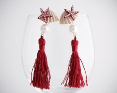 Miss Pretty In the Sea with red tassels earrings. Starfish, shells, and pearls top them off. From www.moxyst.com
