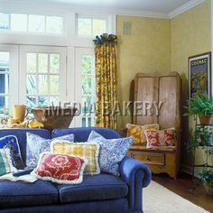 FAMILY ROOM - denim blue sofa, fringed pillows in blue toile, yellow plaid and red floral, yellow sponged walls , white trim, french doors and transoms, french pottery, pine bench with tall back, cognac poster, french country, pot rack holds plants