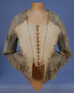 PLAID SILK CARACO JACKET, c. 1770. Narrow sea green vertical stripe over cream and tan horizontal bands, open neck, short angled sleeve, pleated peplum angled at front, all trimmed in wide self furbelows, looped silk cord and tiny tassels, lined in linen with adjustable lacing closure and front stays.