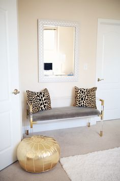 leopard pillows, gold pouf, lucite and gold bench - cute home office!