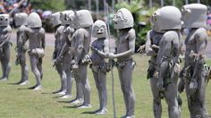 "Traditionally-dressed ""mud men"" prepare to greet the royal couple in Sir John Guise Stadium after a cultural performance in Port Moresby, Papua New Guinea."
