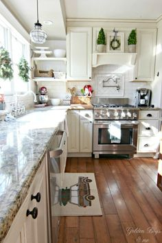 DIY mantel hood in white kitchen with preserved boxwood topiaries