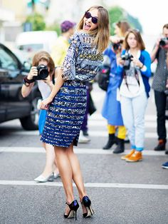 Printed blue shirt, printed blue skirt, multi-colored heels, and sunglasses