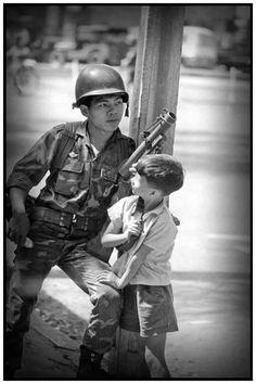 """Ảnh: Người lính hỏi: """"Sau này lớn lên em có ước mơ gì?"""" Cậu bé đáp: """"Sau này lớn lên em sẽ trở thành một người quân nhân giống như anh. Được sống đời trai hùng Tự hào,tự tôn nòi giống Để bảo vệ non nước Việt Nam Để bảo vệ dân lành Việt Nam"""""""