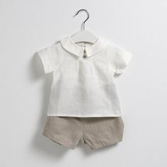 Conjunto compuesto por unas bermudas beige y una blusa con cuello blanca.