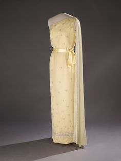 A fan of elegant style, Jackie Kennedy wore a pale, yellow silk evening gown to a White House state dinner in 1961 honoring Tunisian President Habib Bourguiba. Her one-shouldered gown, designed by Oleg Cassini, incorporates elegant details such as a crepe chiffon overlay and a belted sash.