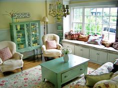 Cottage Living Room - love the bright windows and walls, white woodwork, window seat, comfy covered chairs, pretty area rug, colorful display cabinet and matching chest/table.  Everything!!