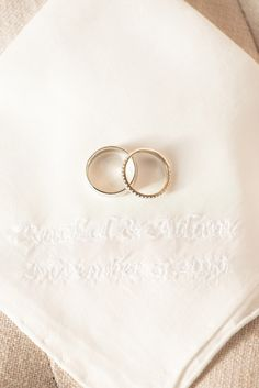 Mikkel Paige Photography photo of a wedding at The Rickhouse, Durham. A picture of the wedding bands against a custom white embroidered handkerchief with the couple's wedding date on it.