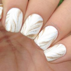 Water marbling has been a trendy nail art technique for a while now, but we particularly love this simple gold-on-white version. #NailArt #NailDesigns