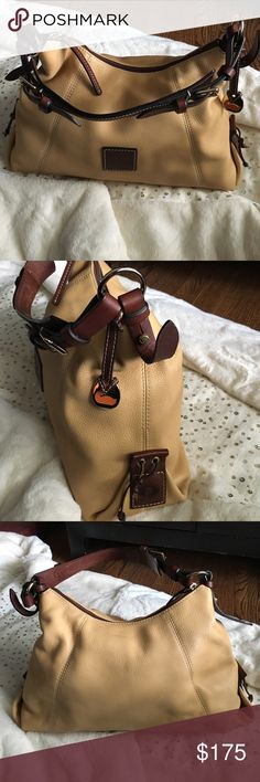 Dooney & Burke bag Light yellow close to tan Dooney & Burke bag with red interior and brown leather buckle with gold hardware...very gently used still look new Dooney & Bourke Bags Shoulder Bags