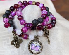 You get exactly whats in the picture, all my jewelry is one of a kind. - THREE BRACELET STACK - you are purchasing THREE bracelets that come together! - Magnificent purple striped agate round beads - Bold black lava stone round beads - Cloudy quartz round beads - Antiquated bronze tone spacer beads - Three lovely charms: butterfly cabochon, antiquated bronze tone fleur-de-lis, antiquated bronze tone key - 7 Inches un-stretched (approximately). These bracelets best fit people with a…