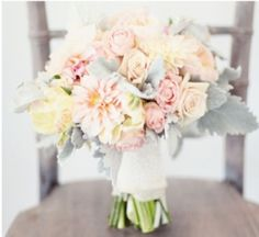 The bridesmaids' bouquet will be a clutch of blush peonies, blush spray roses, blush roses, blush garden roses, blush tulips and grey dusty miller wrapped in navy blue ribbon with the stems showing.