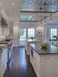 This is an example of a traditional l-shaped open concept kitchen with stainless steel appliances, ceramic backsplash, a farmhouse sink, shaker cabinets, white cabinets, marble countertops, dark hardwood floors, an island and blue backsplash.