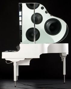 Purists should look away now. A white lacquered baby grand piano shell that houses a projection surface and sound system.