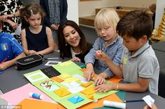 The mother chatted with young pupils who were showcasing their best arts and crafts at the opening of the school in Denmark