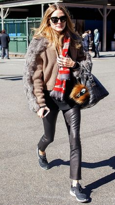 Olivia Palermo wears a knit sweater layered with a fur jacket, leather pants, and Nikes