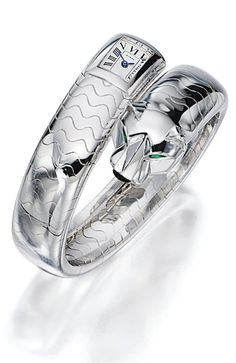 KARAT WHITE GOLD 'PANTHER' BANGLE WRIST WATCH, CARTIER The crossover bangle terminated to one side with a panther head decorated with emerald-set eyes and jet-set nose, to the other side with a rectangular watch dial, mounted in 18 karat white gold, inner circumference approximately 170mm, quartz movement, dial and bangle signed, bangle additionally numbered 22718A.