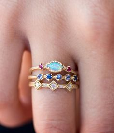 This meticulously hand-crafted ring can't help but stand out amongst the rest. The absolutely radiant opal is surrounded by two vibrant ruby stones. Set in an 18k yellow gold band. All stones are eth