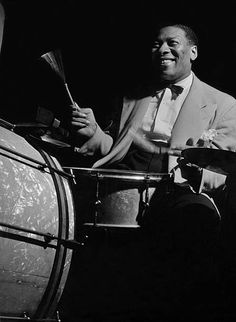 Musician Sidney Catlett, one of the greatest jazz percussionists, playing the drums at a jazz jam session in photographer's Gjon Mili's studio; the large party was organized by Life magazine and attended by the Vogue staff, Mili photographed for Life and Serge Balkin photographed the occasion for Vogue.