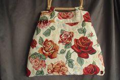 Ausgefallene Stofftasche in einem romantischen Rosendesign in den Farben dunkelrot, grün und beige.  Die Taschengriffe sind aus Holz.    Eine ideale T