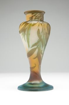 A Galle cameo glass vase, eucalyptus. Circa 1900, cameo signed ''Galle'', the baluster-form body on a spreading circular foot decorated with eucalyptus branches in olive green on a peach and cream ground shaded to blue-green.