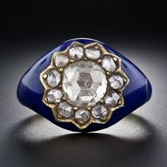 Diamond and Blue Enamel Ring A colorful Georgian/early-Victorian diamond ring highlighting a bright-white half-carat rose-cut diamond orbited by eleven small rose-cut diamonds in a lovely flower, or star, design. The diamonds glisten atop a contrasting and dramatic backdrop of cobalt blue enamel. The enamel has some repair where it meets the gold on the sides. Circa early 19th century. $6,250
