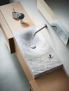 The asymmetrical form of Agape's Cararra marble sink is modeled after the effect of water eroding stone.