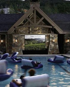 Huge t.v outside with a gigantic pool
