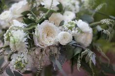 detail of all white bridal bouquet featuring bridal bouquet of  white patience garden rose, white ranunculus, vendela rose, white majolik spray rose, white almond bloom, white scabiosa, dusty miller, seeded eucalyptus, mondial rose & white stock.