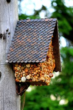 DIY garden birdhouse featuring pebbles and a roof made of pennies