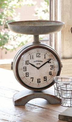 "Dual clock face on antique reproduction scale in rustic gray metal. 14"" x 10"""